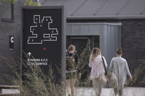 Banner image for Denmark signage. 3 people walking with sign in the front of the map of the building